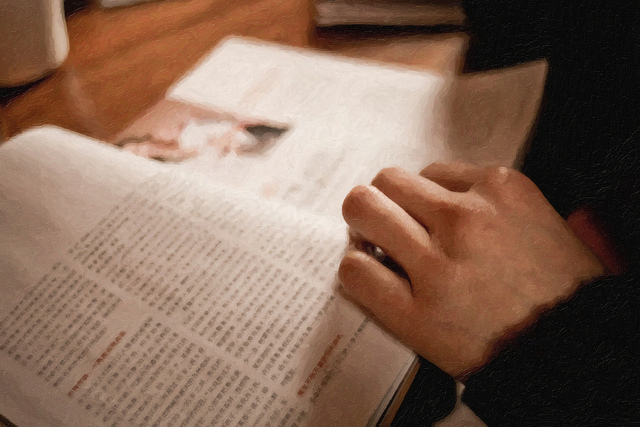 Una persona lee un libro. Sólo se ve su mano sobre el libro