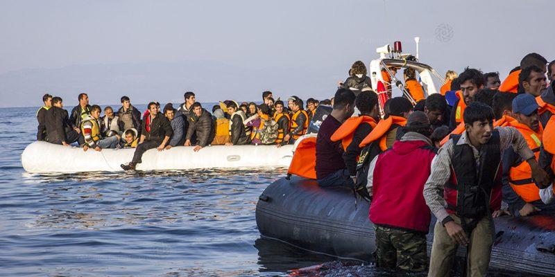 Dos enormes grupos de personas refugiadas en dos botes. Tienen chalecos salvavidas