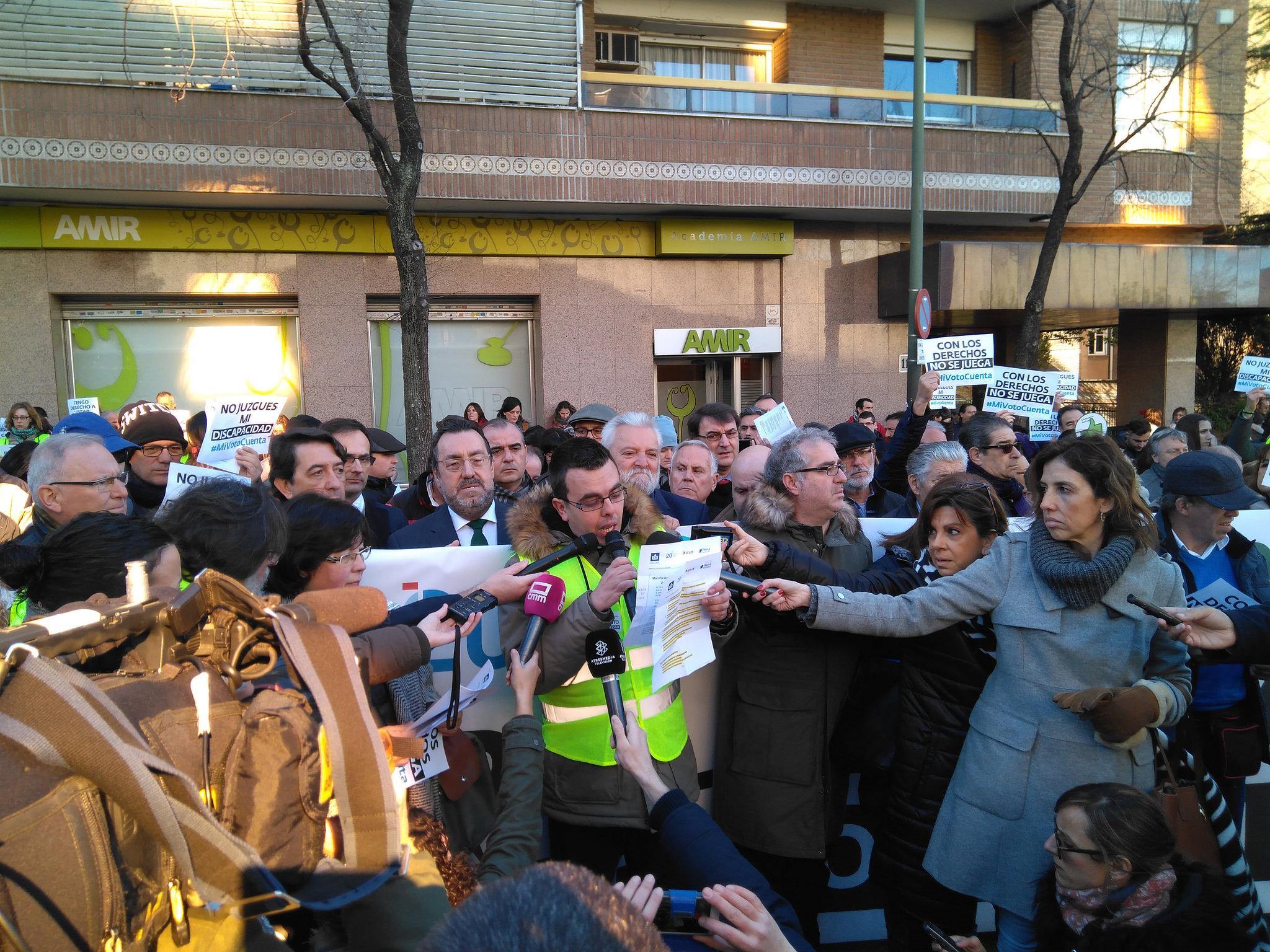 Antonio Hinojosa leyendo el manifiesto por el derecho al voto. Le rodean periodistas y manifestantes