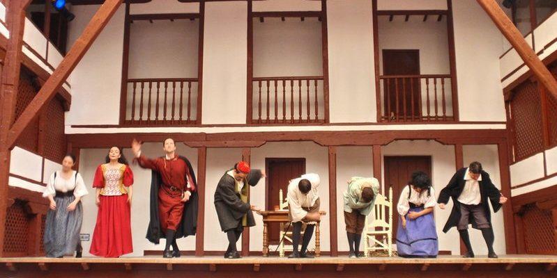 """Representación de """"El médico a palos"""", de Molière. Aparecen las actrices y actores saludando al público. Están en un escenario clásico de madera"""