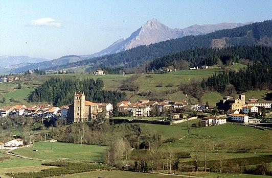 Segura. Se ve un paisaje muy verde, la torre de una iglesia y un pico detrás