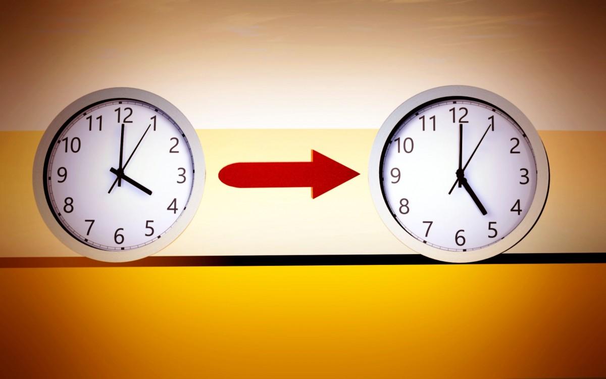 dos relojes con horas diferentes y flecha entre ambos