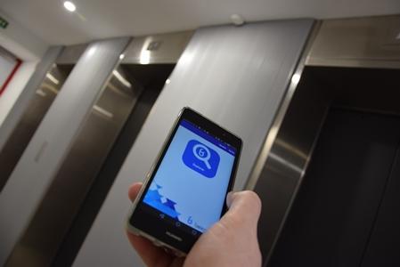 Una mano sujeta un móvil con la app de Beecons abierta. Está en un pasillo