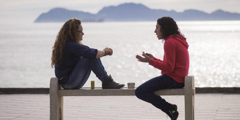 Dos chicas hablan en un banco ante un paisaje de mar y montañas