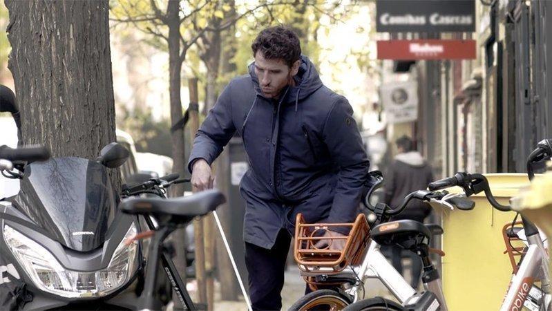 Una persona con bastón blanco detrás de bicis