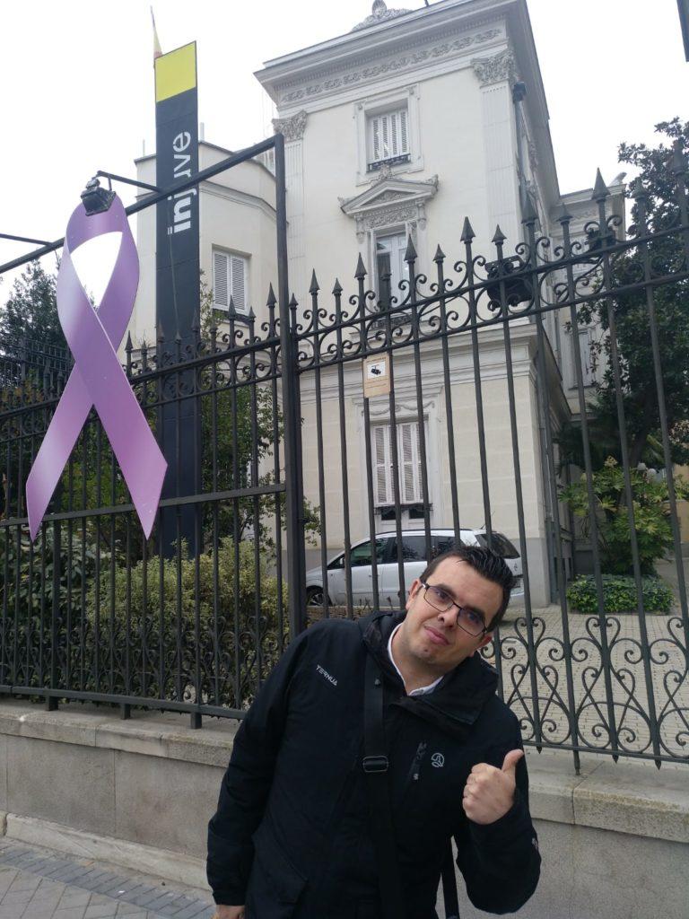 Antonio delante del edificio del INJUVE. El edificio es un palacete. En la entrada hay un lazo morado