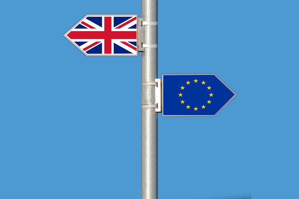 un poste con 2 carteles con las banderas de la Unión Europea y de Reino Unido