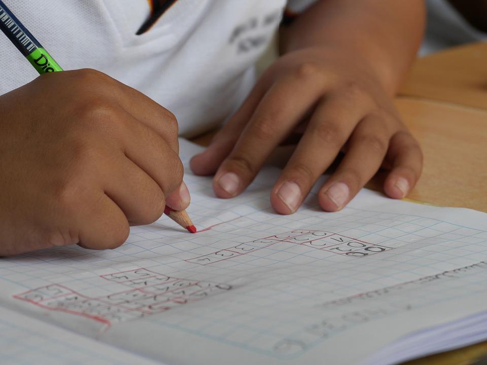 manos de niña hacen cuentas en un cuaderno