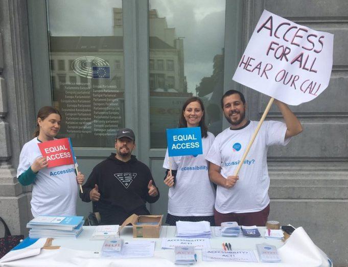 personas recogen firmas con carteles pidiendo accesibilidad