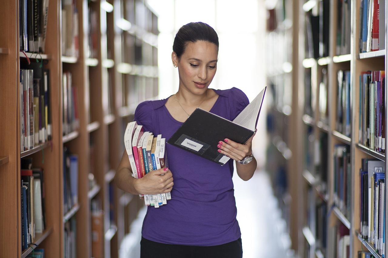 chica con varios libros en una biblioteca