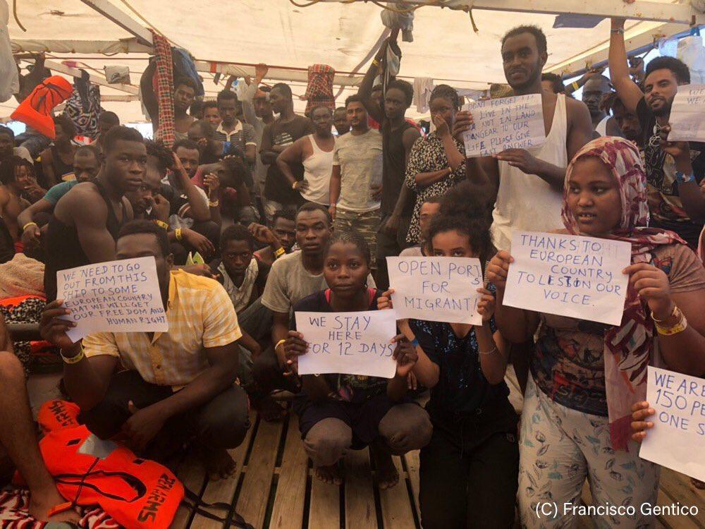 Personas sostienen carteles en el barco
