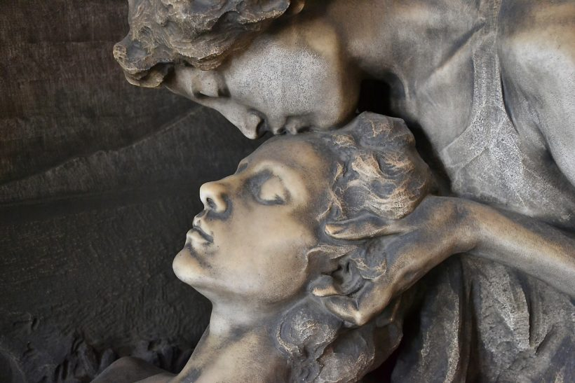 estatua de 2 perosnajes y uno besa en la frente al otro